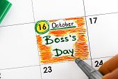 Woman Fingers With Pen Writing Reminder Boss`s Day In Calendar. Close-up. poster