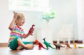 Child Playing With Toy Dinosaurs. Kids Toys. poster