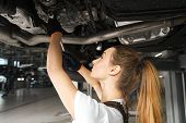 Young Woman Holding Tool, Fixing Car. Girl Working Undercarriage Of Automobile, Auto Lifted On Bridg poster