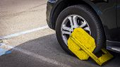 Yellow Tire Clamp On A Tire. Penalty And Fine For Improper Parking. poster