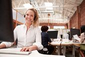 Portrait Of Female Customer Services Agent Working At Desk In Call Center poster