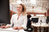 Female Customer Services Agent Working At Desk In Call Center poster