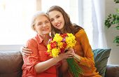 Happy Mothers Day! Adult Daughter Gives Flowers And Congratulates An Elderly Mother On Holiday poster