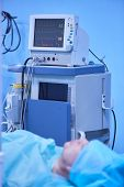 Functional Vital Functions Monitor In An Operating Room With Machines In The Background, During Real poster
