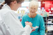 Senior woman in pharmacy talking to the chemist or pharmacist explain effects of a drug poster