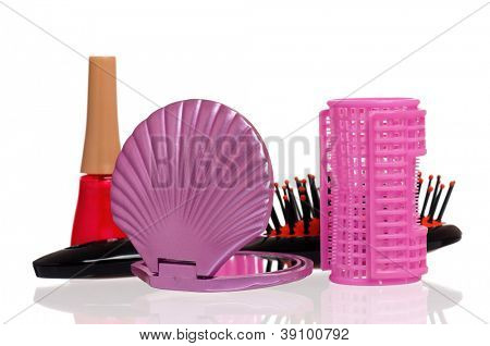 Set of cosmetics - nail polish, hairbrush, hair curlers and small mirror isolated on white background