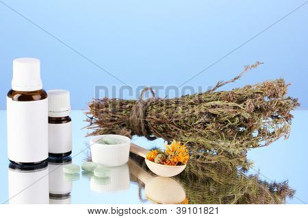 bottles of medicines and herbs on blue background. concept of homeopathy
