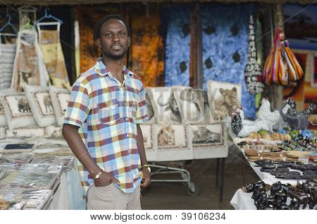 African Curio Salesman Vendor  In Front Of Wildlife Items