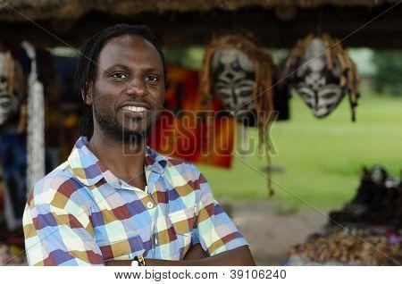 African Curio Salesman Vendor  In Front Of Ethnic Masks
