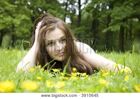 The Girl Lays On A Grass
