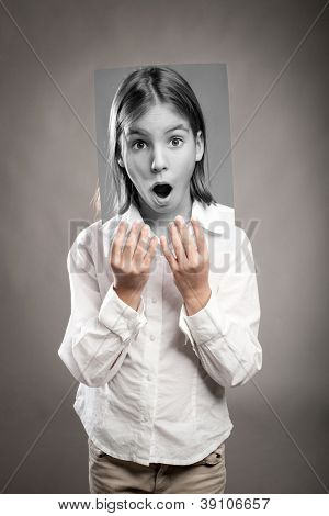 portrait of girl holding a photography of her with surprise expression