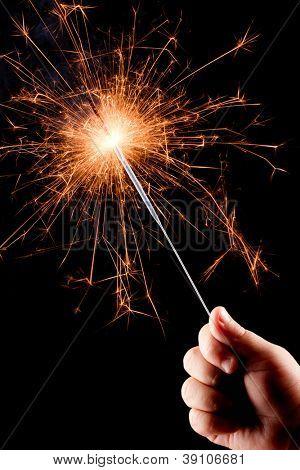 Child's hand, holding a burning sparkler on the black background.