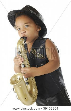 An adorable preschooler playing a toy saxophone in a sparkly black fedora and black leather vest and pants.  On a white background.