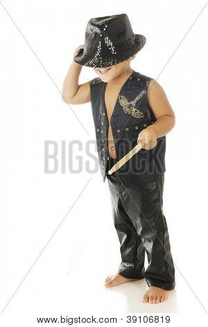 Un niño feliz, pies descalzo en el chaleco de cuero negro y pantalones con un sombrero de fieltro brillante que cubre su ojo