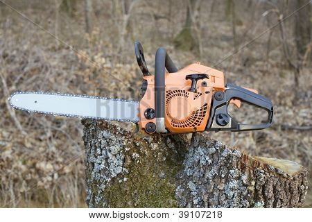 Orange Chain Saw on Log