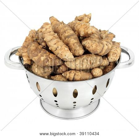 Jerusalem artichoke raw vegetables in a stainless steel colander over white background.