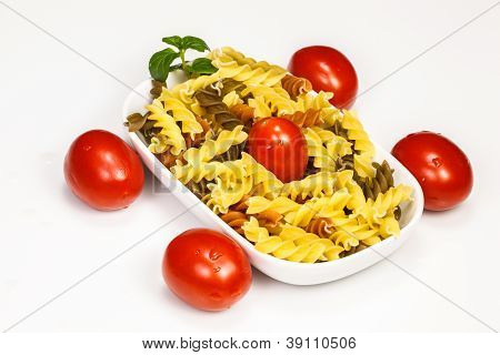 3 color spiral pasta with cherry tomatoes and mint leaf.