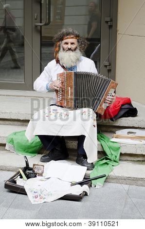 Colorful Man In Traditional Dress Playing The Accordion