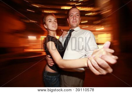 Happy adult couple dancing tango in night New York city