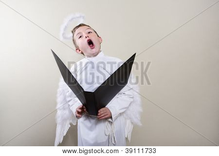 Boy dressed as an angel singing
