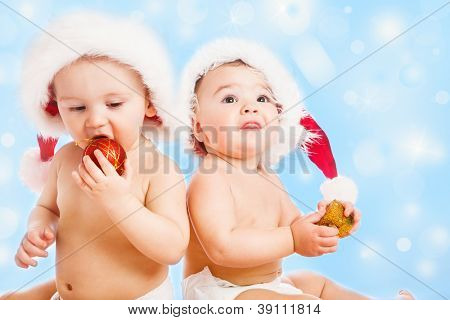 Two sweet baby friends in Santa hats, over blue background