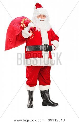 Full length portrait of a Santa Claus holding a bag full of gifts on his back isolated on white background
