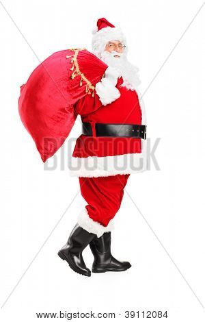 Full length portrait of a Santa Claus walking with bag full of gifts og his back isolated on white background