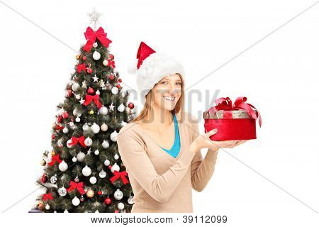 Happy female with christmas hat holding a gift, christmas tree in the background