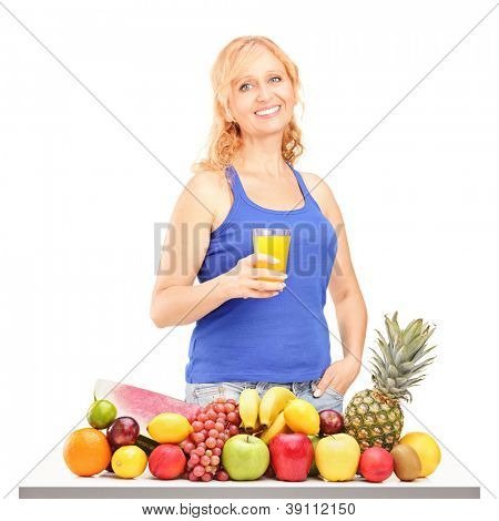 Woman holding glass of orange juice in front of pile of fruit