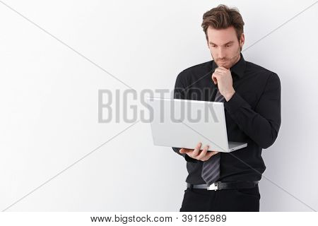 Handsome young businessman working on laptop, standing over white background.