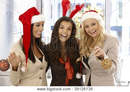 Young businesswomen celebrating Christmas at office wearing santa claus hat.