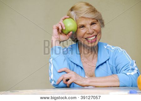 Happy senior woman holding a green apple.