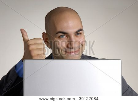 Happy and optimistic businessman working on computer.
