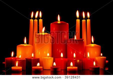 A large group of mixed size and shape candles burning with bright flames on a black background.