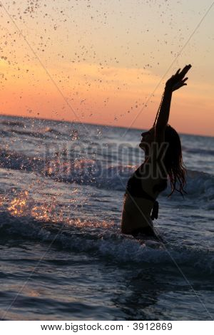 Woman Splashing By Sunset