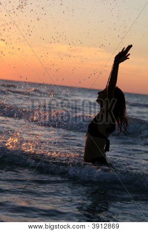Woman Splashing By Sunset
