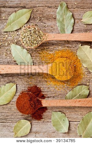 three spices in wooden spoons and bay leaves on rustic wooden background