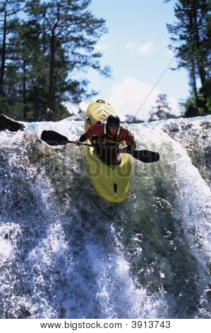 Woman Canoeing Down Steep Water Flow