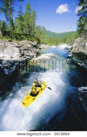 Homem de canoagem em águas rápidas
