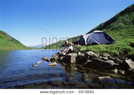 Woman Relaxing By River With Tent