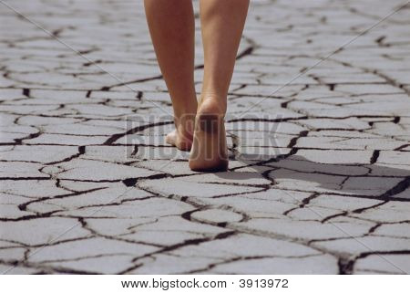 Womans Feet Walking Over Cracked, Rough Terrain