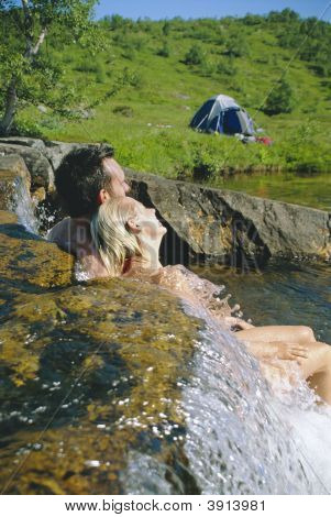 Couple Relaxing In Swimwear By River