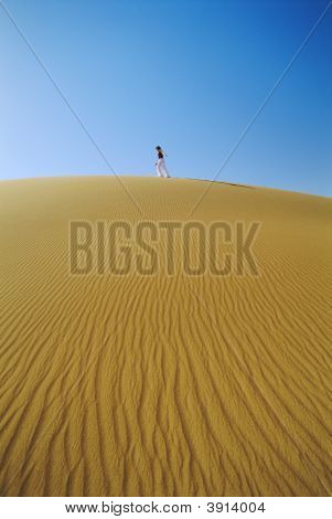 Woman Walking Across Desert