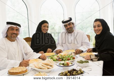 Middle Eastern Couples Sat Around Table Eating Food