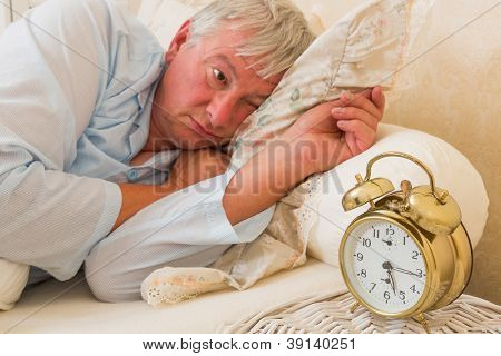 Sleepy elderly man waking up and looking at the alarm clock with one eye - focus is on the alarm clock