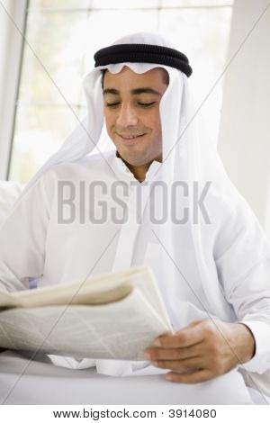 Middle Eastern Man Reading Newspaper At Home
