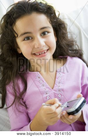 Middle Eastern Child Playing On Blackberry At Home