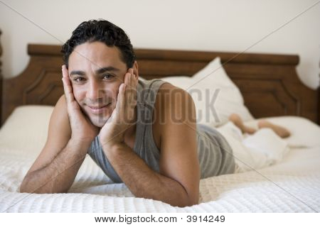 Middle Eastern Man Laid On Bed At Home