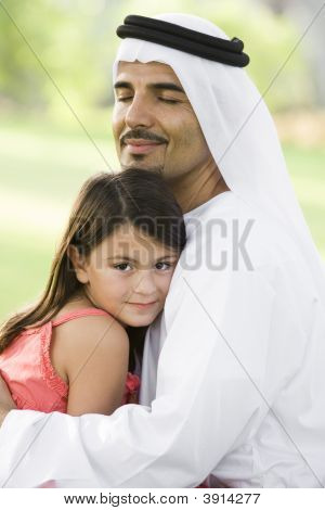 Middle Eastern Man Sat On Grass In Park With Daughter