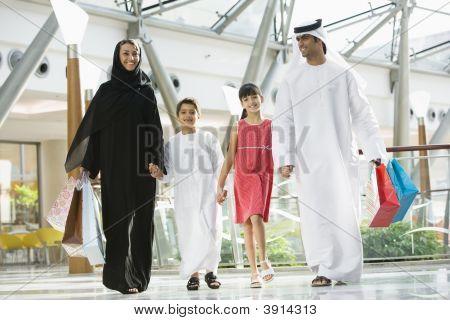 nahöstlichen Familie zu Fuß durch Einkaufszentrum mit Taschen